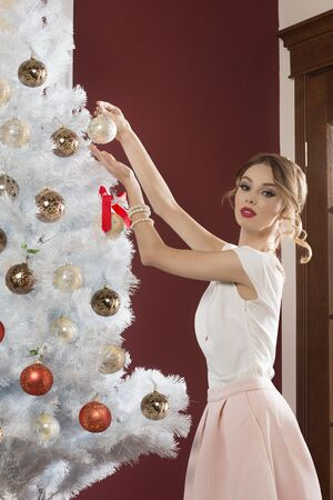 elegant girl: elegant girl with hair-style, stylish make-up and pearl jewels decorating christmas tree in indoor portrait
