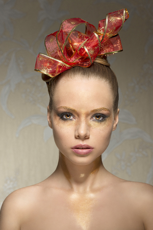 nude christmas: close-up beauty shoot of stunning female with naked shoulders, freckles and artistic christmas glossy golden make-up and red ribbon in the elegant hair-style.