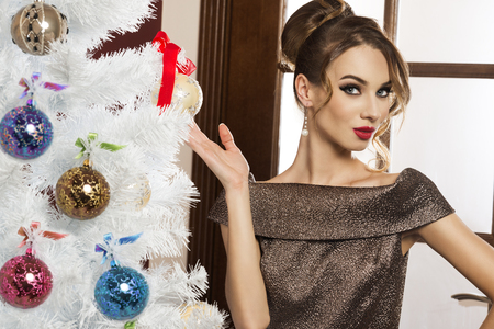 hair do: stunning portrait of young brunette , very elegant , near the christmas tree , looking in camera with her blue eyes . make up and hair do