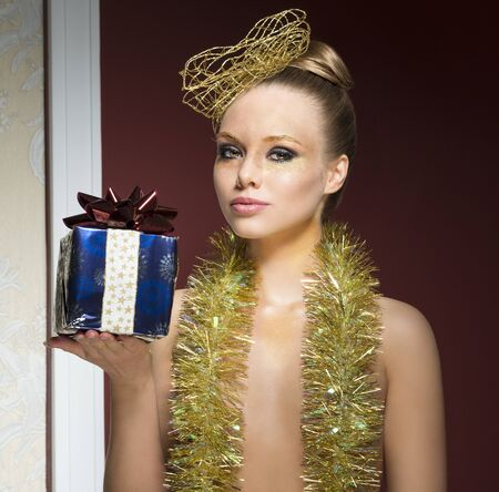 nude christmas: beauty close-up christmas portrait of charming female with christmas creative glossy make-up, golden accessory in the hair-style, tinsel on her naked breast and gift box in the hand Stock Photo