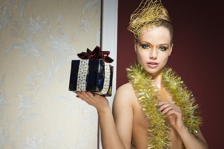 stunning woman with creative golden make-up and hair-style posing in christmas portrait with gift box in the hand and tinsel on her naked breast