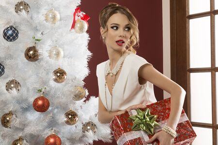 female christmas: beautiful woman with sly expression, elegant clothes, hair-style and pearl necklace taking gift box in the hand near decorated christmas tree. Xmas holidays