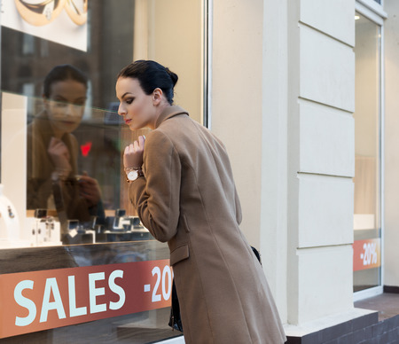 desire: beautiful elegant woman , outdoor for shopping , looking at jewellery windiw shop with desire. Stock Photo