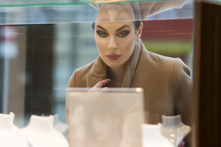 looking inside: fashion brunette in front of window shop looking inside for a present .wearing a coat. reflection of glass on face