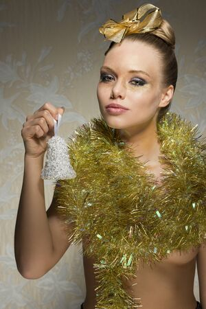 sexy girl with freckles posing in creative christmas portrait with golden ribbon in the hair-style, christmas glossy make-up and shiny tinsel around neck. Taking little bell in the hand