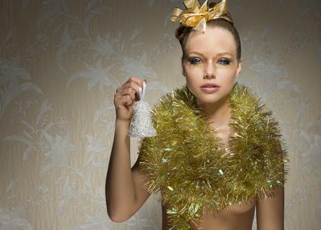 desnudo artistico: impresionante mujer con pecas posando en sesi�n de navidad art�stica con la campanilla en la mano, la cinta de oro en el estilo del cabello, navidad brillante maquillaje y oropel alrededor del cuello.