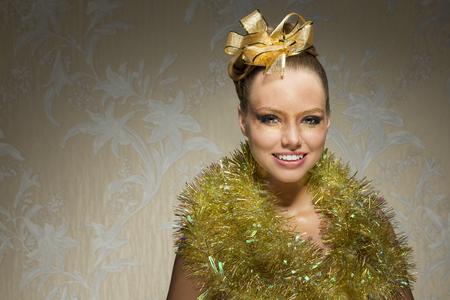 desnudo artistico: creativa sesi�n de navidad de la sonrisa feliz hembra con pecas, oropel alrededor del cuello, cinta de oro en el estilo del cabello y de la Navidad brillante maquillaje.