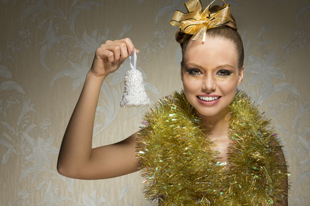 nude young woman: smiling happy female with freckles and artistic christmas look. Posing with shiny tinsel around neck, golden ribbon in the hair-style and christmas glossy make-up. Taking little bell in the hand