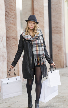 winter fashion: pretty woman , with hat and scarf, walking on a street ready for shopping , in a wi nter sale. looking in camera Stock Photo