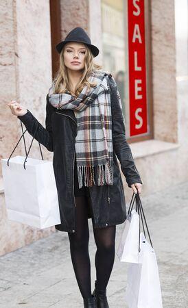 mujer alegre: La muchacha bonita, para ir de compras fuera de invierno, que lleva una bufanda y un sombrero negro de la chaqueta. ella está carryng algunas bolsas. mirando en la cámara.
