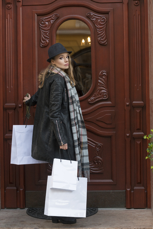 looking after: beautiful young lady , with hat and scarf , coming back home after shopping , she bring some shopper , she looking in camera Stock Photo