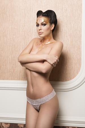 modelos desnudas: señora hermosa morena posando con su cuerpo desnudo atractivo, ropa interior de encaje de oro brillante y creativo de maquillaje y peinado. Cubre su pecho y mirando a puerta cerrada