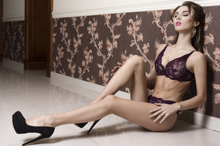 erotic woman: stunning brunette woman with sexy lingerie and heels sitting in erotic pose on floor in elegant interior ambient