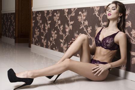 femmes nues sexy: superbe femme brune avec de la lingerie sexy et talons assis dans la pose érotique sur le sol, dans l'élégant ambiante intérieure
