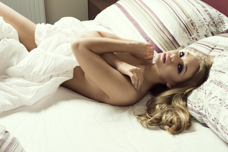 nude blonde woman: cute young blond woman , laying down on bed ,coverung body with sheet . she is looking very sensual in camera Stock Photo