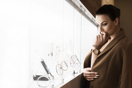 mujeres elegantes: joven impresionante, de interior cerca de una tienda ventana, mirando la joya y pensando en lo mejor para comprar, un disparo en la luz ambiente natural.