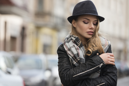 urban fashion: lifestyle shot of young pretty woman with scarf and hat , in urban situation , she has freckles on face . winter dress. she is looking down