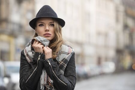 fall time: fashion shot portrait . outdoor in city contest , pretty young woman with freckles , wearing scarf and hat , in fall time Stock Photo