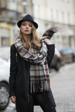 urban fashion: fashion shot of very cute model , in urban style , on the road , she is wearing scarf and hat . freckles on face . scarf and hand moving