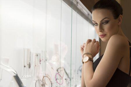 mujer alegre: Morena muy agradable, en la luz natural ambiente, cerca de una ventana de la tienda, buscando un poco de joyería.