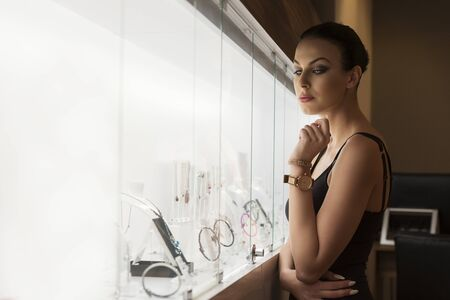 indoor inside: Stunning young brunette , watching jewel inside a jewellery , she stand near the shop window indoor .