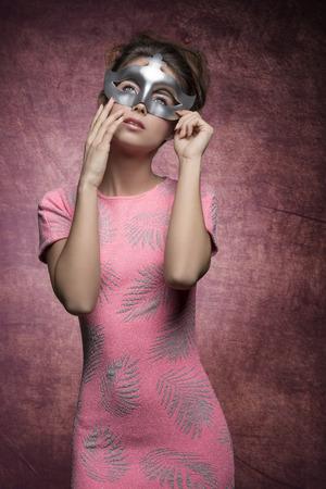 affascinante ragazza con sexy abito rosa e capelli stile che propone con la maschera d'argento e di espressione romantica