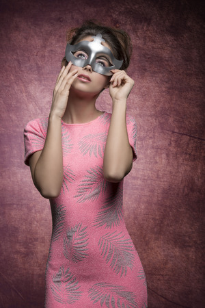 charming girl: charming girl with sexy pink dress and hair-style posing with silver mask and romantic expression