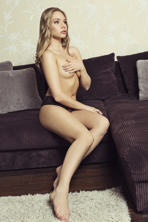 mujer rubia desnuda: interior Retrato de mujer rubia erótica con el cuerpo desnudo llevaba bragas de encaje únicos, que cubre su pecho y sentado en el sofá. Sexy glamour pin-up con frekles en la cara Foto de archivo