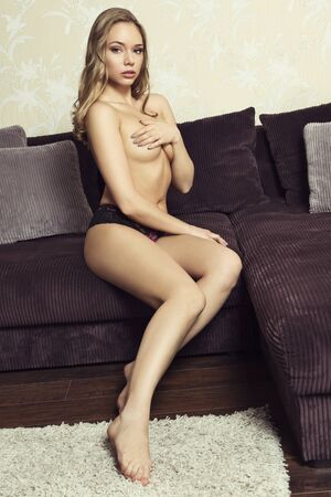woman naked body: sexy blonde woman wearing only lace panties, with perfect body, sitting on velvet couch in pin-up pose and covering her naked breast. Freckles on face Stock Photo