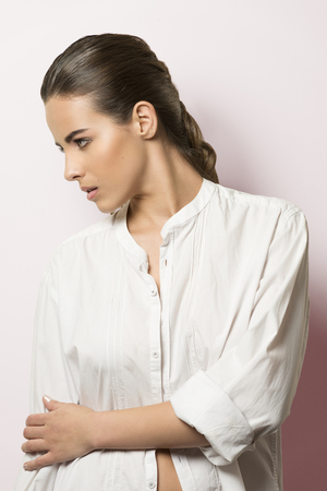 open shirt: cute fashion portrait of very beautiful female with natural make-up and perfect skin. Turned on her profile wearing white open shirt