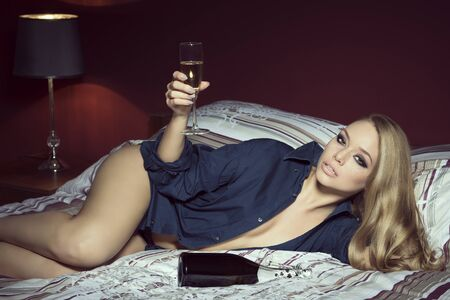 night shirt: luxurious glamour interior portrait of stunning blonde woman with freckles, make-up, long blonde hair and open shirt lying on comfortable bed with a bottle of champagne and a glass of drink in the hand