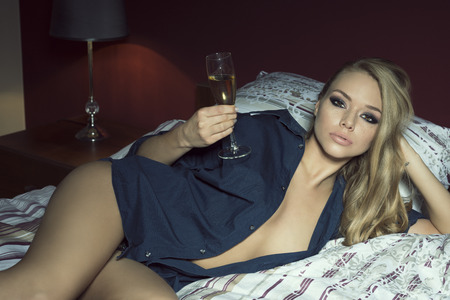 molto sexy donna bionda con lunghi capelli biondi, lentiggini sul viso, elegante make-up, slip e camicia blu aperta sdraiato sul letto con un bicchiere o champagne in mano. Guardando a porte chiuse
