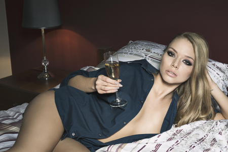 inebriated: stunning blonde woman with freckles on visage lying on bed with stylish make-up, blue open shirt, panties and a glass of champagne in the hand. Sexy night romantic party