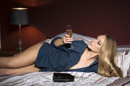 ragazze bionde: coperto ritratto di molto sexy ragazza bionda con le lentiggini, il make-up, capelli biondi lunghi, camicia aperta e mutandine. Sdraiato sul letto confortevole con una bottiglia di champagne e un bicchiere di bevanda in mano