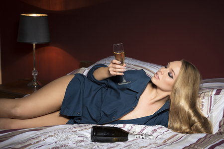 inebriated: Indoor portrait of very sexy blonde girl with freckles, make-up, long blonde hair, open shirt and panties. Lying on comfortable bed with a bottle of champagne and a glass of drink in the hand