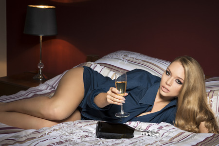 charming blonde woman in luxurious situation in bedroom. lying in sensual  pose on bed with a glass and bottle of champagne, stylish make-up and open sexy shirt. freckles on visage