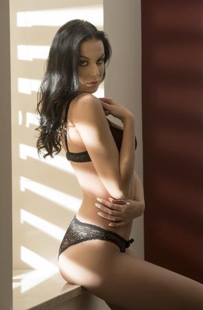 mujeres eroticas: chica muy atractiva que presenta cerca de la ventana interior en luz de la mañana con el pelo largo y negro y ropa interior de encaje. Buscando en la cámara