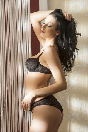 mujer sexy desnuda: Interior retrato del encanto de la mujer atractiva con un cuerpo perfecto y llevaba ropa interior larga del cordón del pelo negro