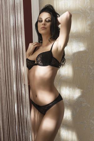 mujer sexy desnuda: mujer atractiva con ropa interior de encaje negro y el pelo largo que presenta en retrato del encanto de interior Foto de archivo