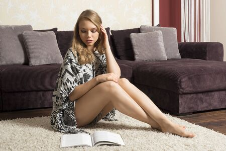ethnic dress: beautiful girl wearing an ethnic dress , she is sitting on carpet in livingroom of her nice home , reading a book