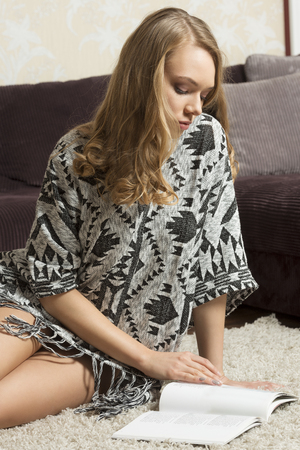 ethnic dress: pretty caucasian girl , in ethnic dress , sitting on a carpet in her livingroom , in act to read a book . she looks down