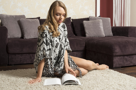 ethnic dress: prettty girl wearing an ethnic dress , she is sitting on carpet in livingroom of her nice home , she is reading a book Stock Photo