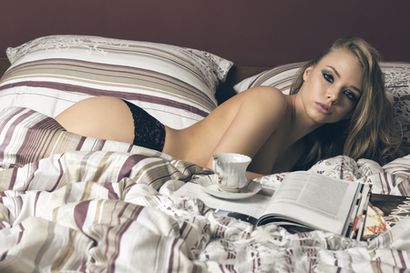 nude in bed: beautiful female with freckles and long natural hair, posing laying on bed with nude body and lace panties, a cup of tea or coffee and some magazines. Looking in camera