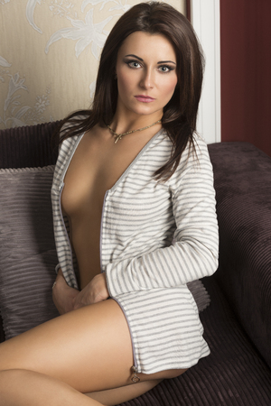 naked sexy women: glamour portrait in natural light of pretty brunette woman sitting on sofa with open jacket on her naked sexy body. She is looking in camera Stock Photo