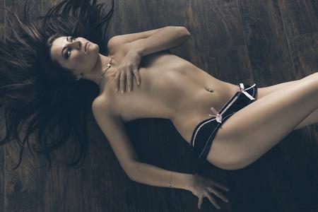 mujeres eroticas: chica pinup erótica morena con el pelo largo y elegante maquillaje se extiende en el piso de madera con el cuerpo desnudo y sólo bragas atractivas. Ella está cubriendo su pecho Foto de archivo