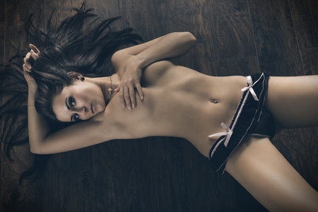 sexy breasts: sexy female with perfect naked body in erotic pose lying on wood floor, she is wearing only panties and covering her naked breast. Stock Photo