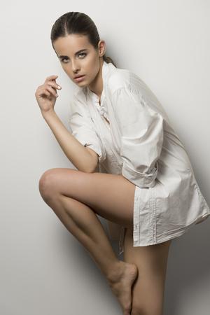 belle brune: belle femme brune avec délicate maquillage, portant chemise déboutonnée et les jambes nues. Dans la mode pose, elle regarde dans la caméra avec une charmante expression