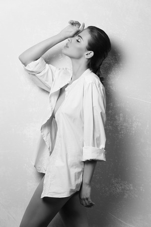 woman white shirt: black and white , beautiful woman with brown hair and perfect skin in fashion pose with unbuttoned white shirt and nude legs