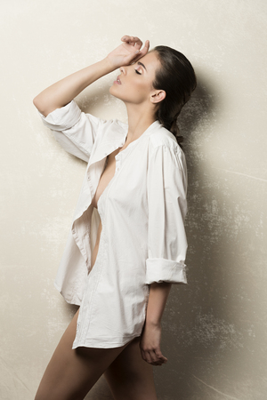 woman white shirt: beautiful woman with brown hair and perfect skin in fashion pose with unbuttoned white shirt and nude legs