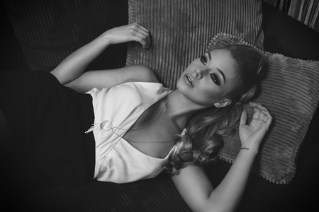 black and white image of very cute and sweet blond young woman , laying on the sofa , she has elegant dress , and long hair . she is looking up with a dreaming expression